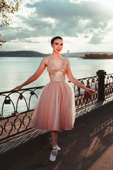 Une jeune ballerine élégante vêtue d'une robe rose avec une jupe ample en organza une ballerine pose près d'un ...