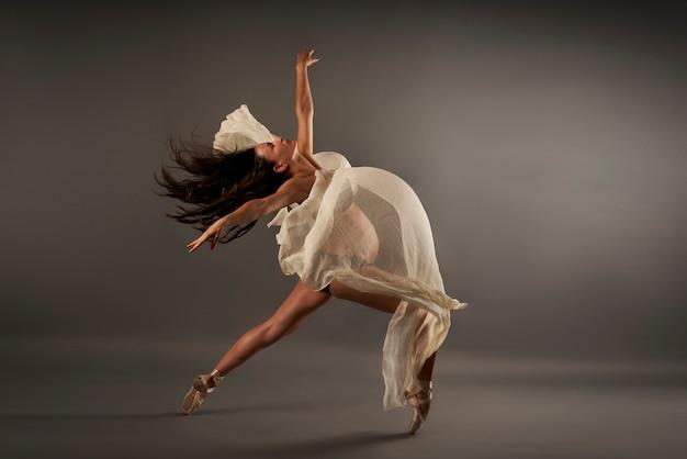 Jeune ballerine enceinte effectuant une pose de ballet classique avec un chiffon de soie