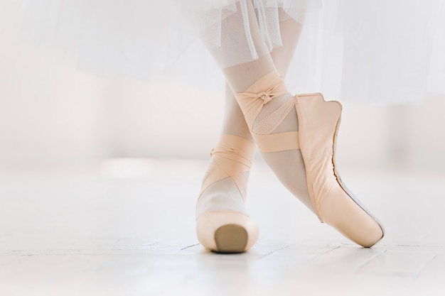 Jeune ballerine, gros plan sur les jambes et les chaussures, debout en position de pointe.