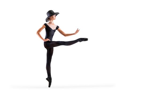 Jeune ballerine en pointes noires et un élégant chapeau posant sur fond blanc