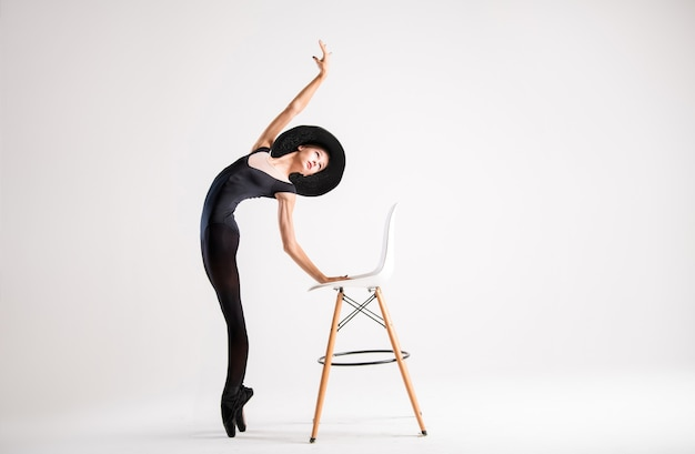Jeune ballerine en pointes noires et un élégant chapeau vole avec une chaise sur fond gris