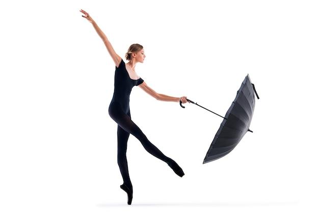 Une jeune ballerine en pointes noires et justaucorps posant avec parapluie dans une pose gracieuse isolée sur fond blanc