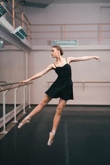 Jeune ballerine pratiquant dans le studio de danse