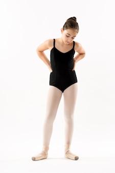 Jeune ballerine réfléchie avec les mains sur les hanches