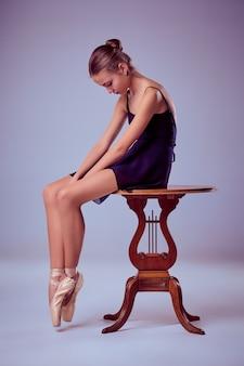 Jeune ballerine en robe bleue assise sur une chaise en bois sur fond lilas ballerine