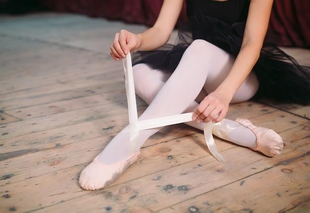 La jeune ballerine en robe noire entraîne dans les coulisses.