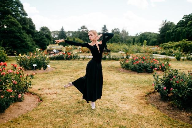 Jeune ballerine en robe noire posant et montrant des poses de ballet dans le parc d'été.