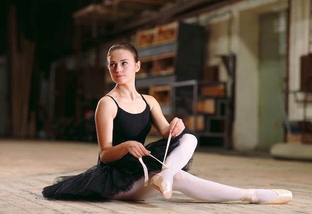 Une jeune ballerine en robe noire s'entraîne dans les coulisses.