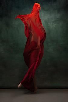 Jeune ballerine tendre gracieuse sur un espace studio vert foncé avec un chiffon rouge