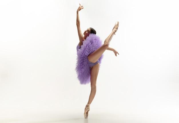 Jeune ballerine tendre gracieuse sur fond de studio blanc