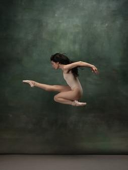 Jeune ballerine tendre gracieuse sur fond de studio vert foncé