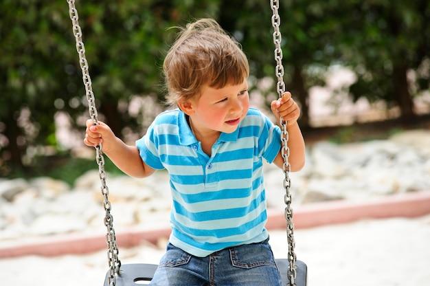 Un jeune bambin se balançant dans les balançoires de la chaîne.