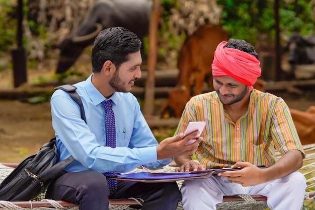Jeune banquier ou agronome indien montrant des détails à un agriculteur sur un smartphone.
