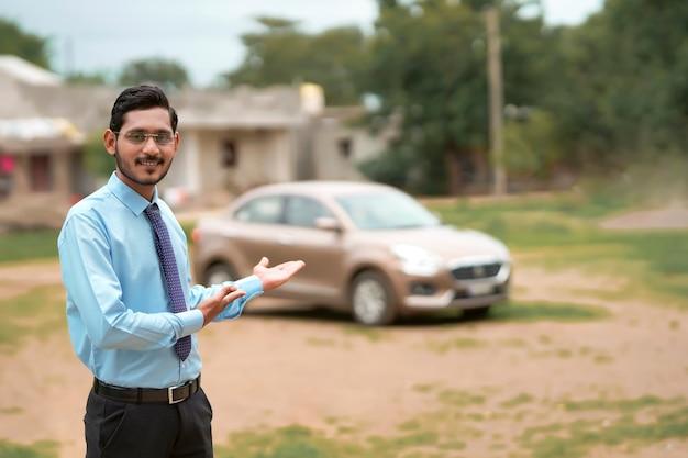 Jeune banquier ou financier indien debout avec une voiture