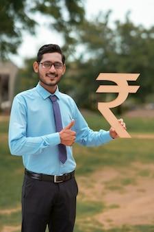 Jeune banquier ou financier indien tenant le symbole de la roupie à la main