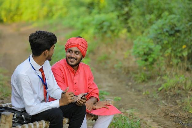 Jeune banquier indien discuter avec l'agriculteur au champ