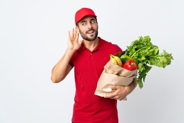 Jeune, barbe, tenue, sac, plein, legumes, isolé, blanc, mur, écoute, quelque chose