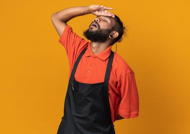 Jeune barbier afro-américain fatigué en uniforme gardant la main derrière le dos et sur le front avec les yeux fermés