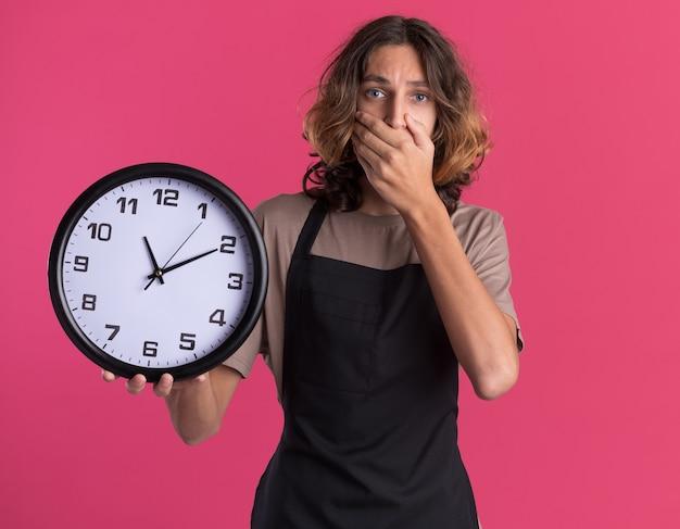 Jeune barbier beau portant l'uniforme tenant l'horloge regardant l'avant mettant la main sur la bouche isolée sur le mur rose