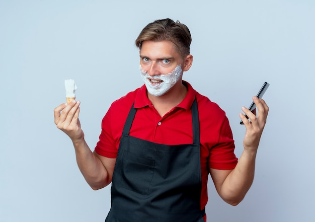 Jeune barbier blond excité en uniforme visage enduit de mousse à raser holding blaireau de rasage