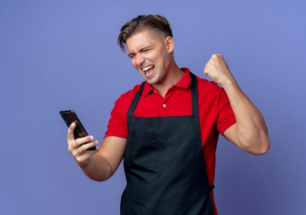 Jeune barbier blond joyeux en uniforme lève le poing en regardant le téléphone