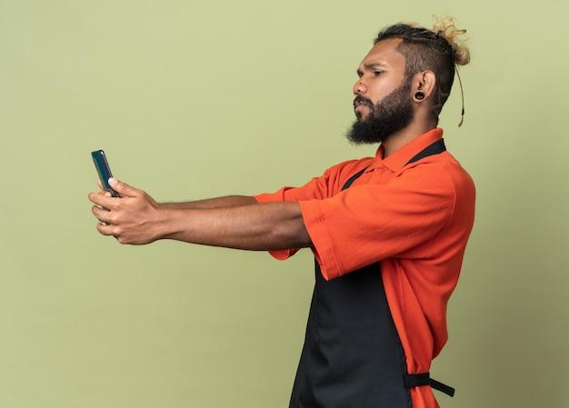Jeune barbier fronçant les sourcils en uniforme debout en vue de profil prenant selfie isolé sur mur vert olive
