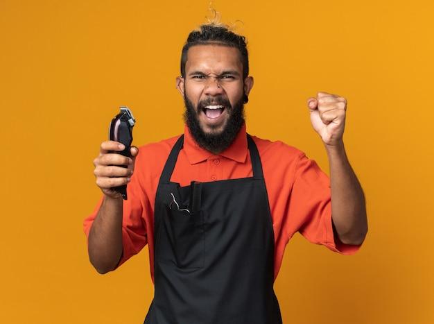 Jeune barbier masculin afro-américain joyeux portant l'uniforme tenant des tondeuses à cheveux faisant un geste oui