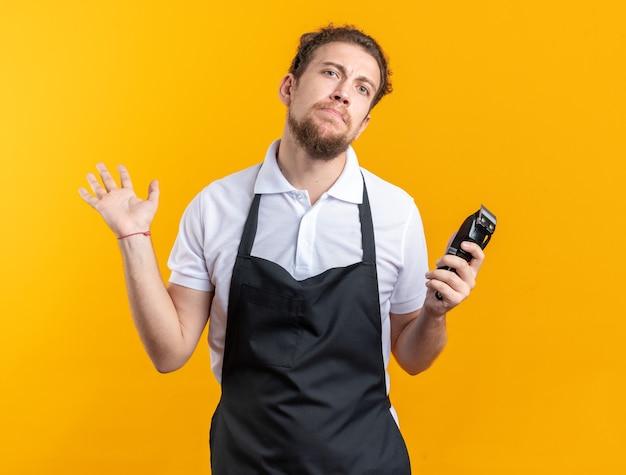 Jeune barbier masculin confus en uniforme tenant une tondeuse à cheveux isolée sur un mur jaune