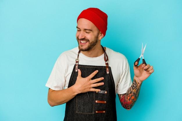 Jeune barbier tatoué isolé sur fond bleu rit fort en gardant la main sur la poitrine.