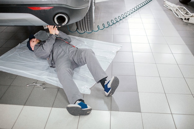 Jeune barbu est allongé sous la voiture et tient un long tube avec les mains. il est sérieux et concentré. l'homme travaille.
