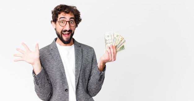 Jeune barbu fou avec des billets en dollars