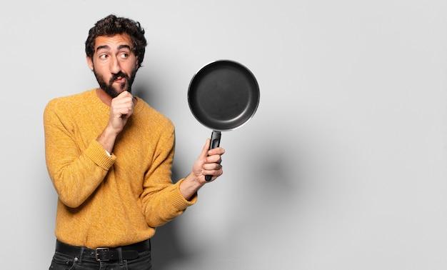 Jeune barbu fou avec une casserole. concept de cuisinier