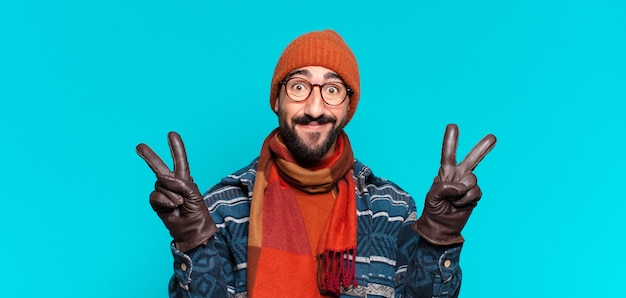 Jeune barbu fou célébrant un triomphe comme un gagnant et portant des vêtements d'hiver
