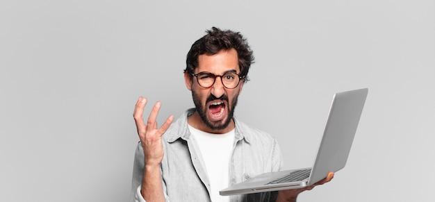 Jeune barbu fou. concept d'ordinateur portable