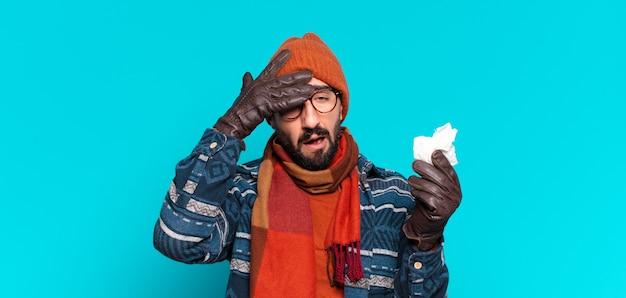 Jeune barbu fou et portant des vêtements d'hiver. notion de maladie