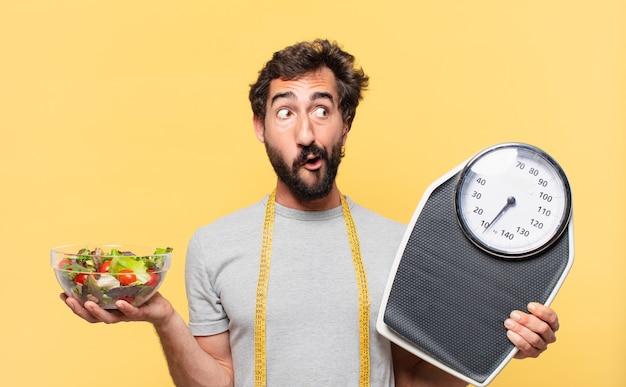 Jeune barbu fou suivant un régime doutant ou d'expression incertaine et tenant une balance et une salade