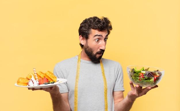 Jeune barbu fou suivant un régime doutant ou d'expression incertaine et tenant une salade et des gaufres