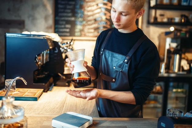 Jeune barista masculin fait un expresso frais
