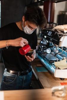 Un jeune barista avec un masque médical prépare un délicieux café cappuccino avec du café dans un café. concept de protection covid-19 et pandémie