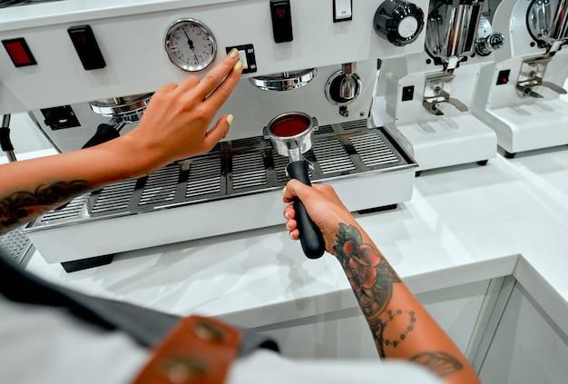 Une jeune barista séduisante attache un porte-filtre à une machine dans un café.