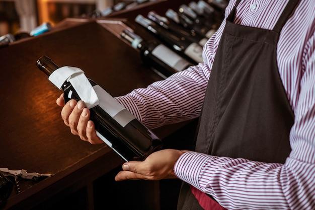 Jeune barman posant en uniforme debout parmi les étagères en bois sombre