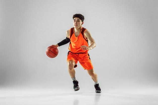 Jeune basketteur de l'équipe portant une formation de vêtements de sport, pratiquant en action, mouvement en course isolé sur mur blanc. concept de sport, mouvement, énergie et mode de vie dynamique et sain.