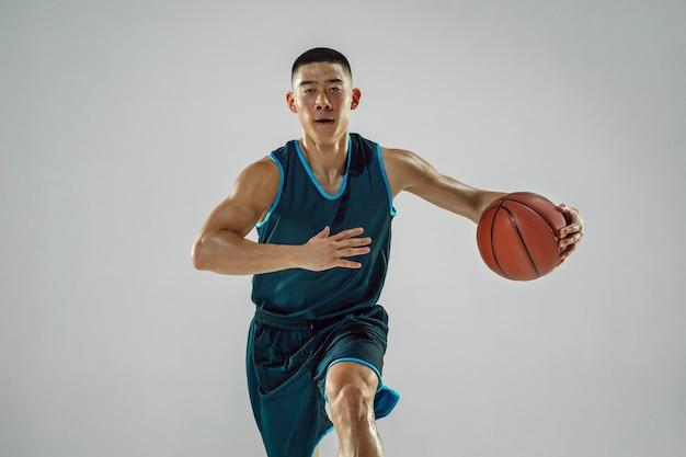 Jeune basketteur de l'équipe portant la formation de vêtements de sport, pratiquant en action, mouvement en course isolé sur mur blanc