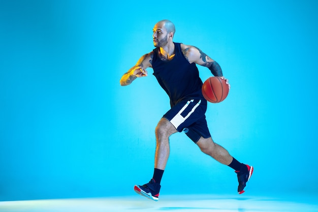 Jeune basketteur de l'équipe portant la formation de vêtements de sport, pratiquant en action, mouvement isolé sur mur bleu en néon. concept de sport, mouvement, énergie et mode de vie dynamique et sain.