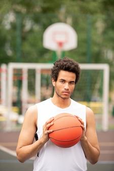 Jeune basketteur interculturel en t-shirt blanc tenant le ballon par la poitrine pendant le jeu sur le court