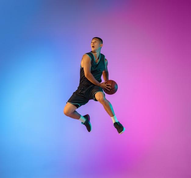Jeune basketteur en mouvement sur fond de studio dégradé en néon