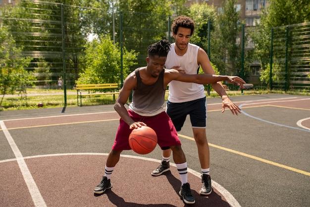 Jeune basketteur professionnel défendant la balle contre l'attaque du rival pendant le jeu sur le terrain