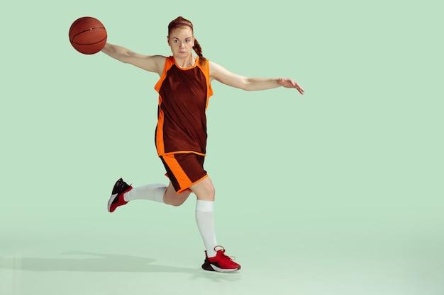 Jeune basketteuse caucasienne en action, mouvement pendant le jeu isolé sur fond de couleur menthe. concept de sport, mouvement, énergie et mode de vie sain et dynamique. entraînement, pratique.