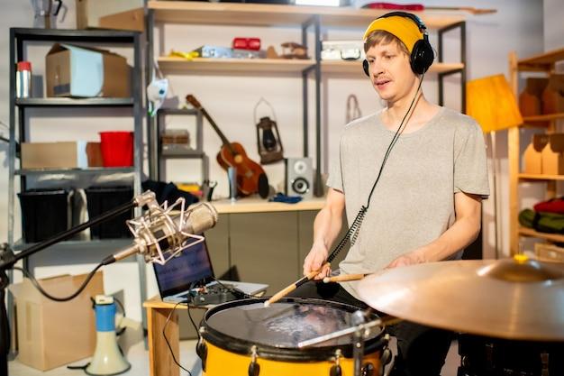 Jeune batteur avec des écouteurs battant le tambour avec des baguettes pendant la répétition individuelle et l'enregistrement de sa musique devant le microphone