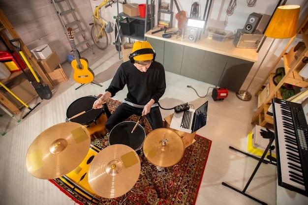 Jeune batteur avec des écouteurs tenant des baguettes sur cymbale et tambour tout en allant les battre lors d'une répétition individuelle